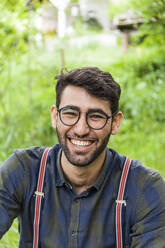 Portrait of laughing young man wearing glasses - TCF06289