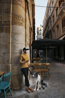 Man wearing protective mask waiting with his dog in the city - AGGF00087