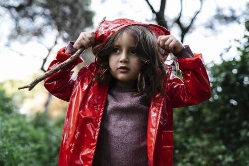 Girl wearing red rain jacket and hood in the woods - EGAF00271