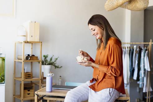 Female fashion designer having lunch break in home office - ERRF04060
