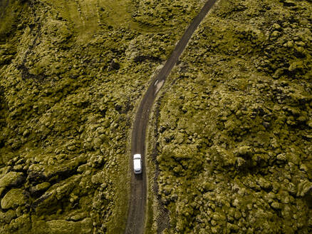 Aerial view of car driving through moss covered lava rocks in Ic - CAVF85786