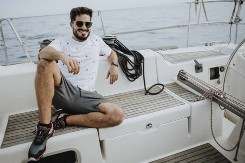 Smiling young man wearing sunglasses sitting in sailboat - GMLF00307