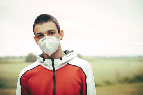 Portrait of teenager wearing protective mask outdoors - ACPF00762