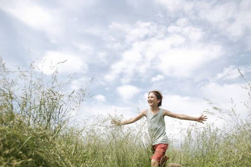 Portrait of happy boy running on a field with arms outstretched - EYAF01181