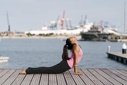 Woman practicing cobra pose on pier against sea at harbor - EGAF00319