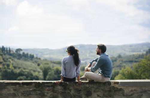 Woman photographing boyfriend sitting on retaining wall in Florence, Italy - SODF00763