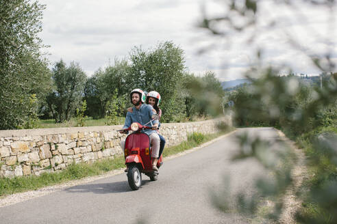 Couple enjoying road trip on Vespa, Tuscany, Italy - SODF00775