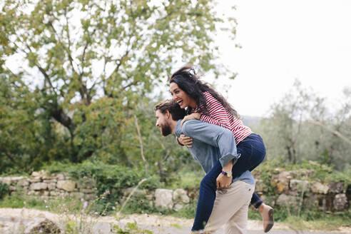 Happy man piggybacking girlfriend while running outdoors - SODF00778