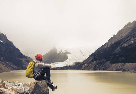 Man with backpack sitting on rock by lake at Patagonia, Argentina - UUF20704