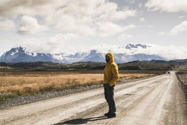 Man standing on dirt road against sky at Torres Del Paine National Park, Patagonia, Chile - UUF20734