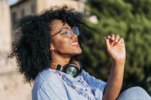 Portrait of smiling woman with afro hair and headphones - JAF00007