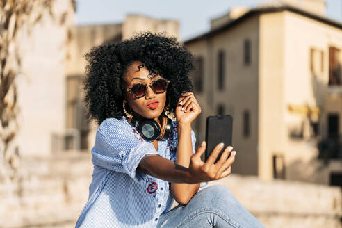 Smiling woman with afro hair and sunglasses taking a selfie with her smartphone - JAF00010