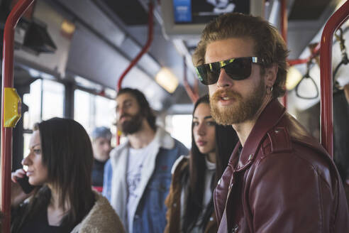 Bearded young man with friends traveling in bus - MEUF01043