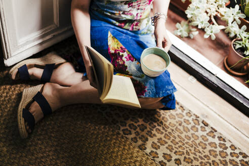 Woman holding coffee cup and book while sitting on floor at home - EBBF00300