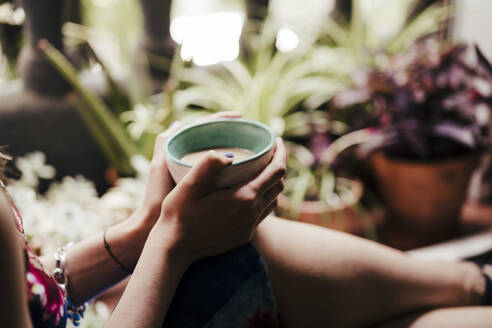 Close-up of woman's hands holding coffee cup - EBBF00303