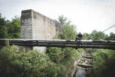 Drone shot of man with sword sitting on old pipes against sky - HMEF00961