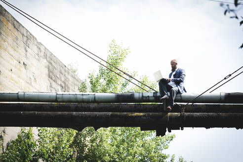Bald businessman wearing suit using laptop while sitting on old pipes against sky - HMEF00964