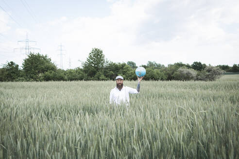 Bearded man holding globe while standing amidst cornfield against sky - HMEF01009