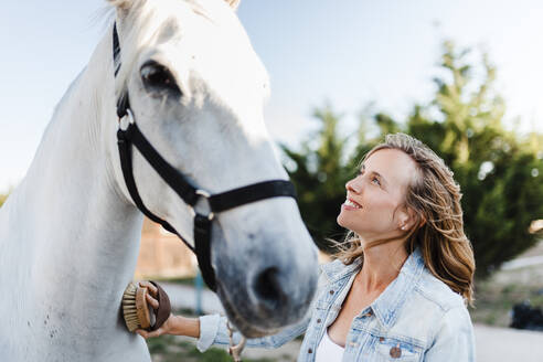 Smiling woman brushing a horse on a farm - MRRF00091
