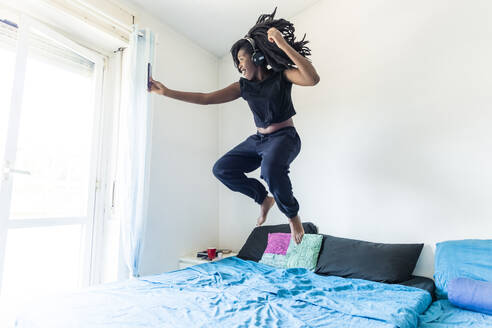 Young woman using smartphone and listening music jumping on bed - MEUF01074