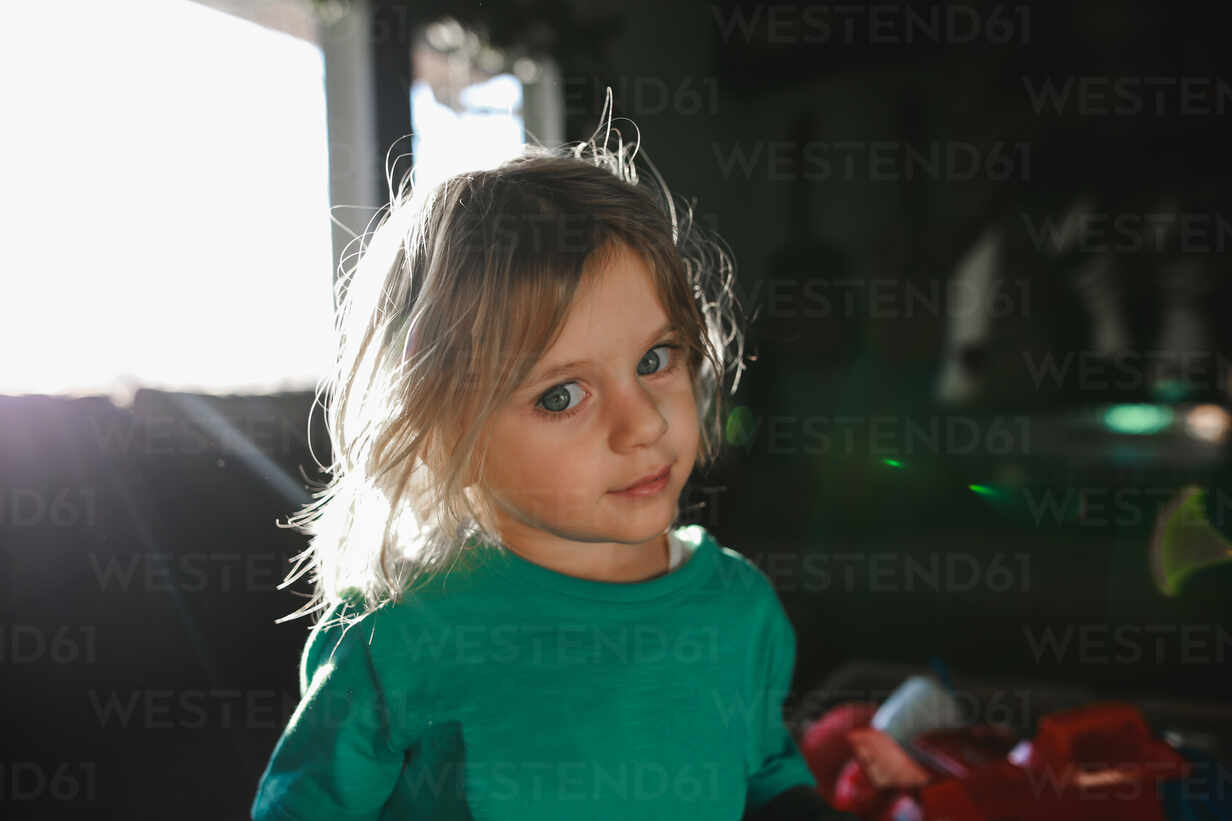 Little Boy With Long Hair Looking At Camera With Sunflare From Window Cavf86502 Cavan Images Westend61