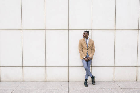 Young businessman leaning against a wall looking sideways - ABZF03210