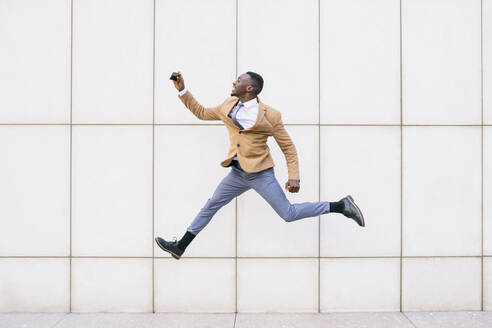 Young businessman jumping and taking a selfie in front of a wall - ABZF03219