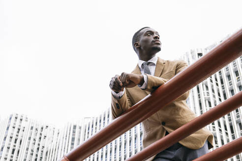 Young businessman leaning on a railing in the city looking away - ABZF03231