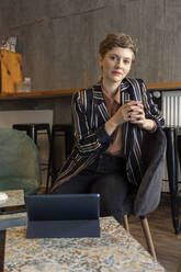Portrait of freelancer sitting in a coffee shop with digital tablet and smartphone - TAMF02433