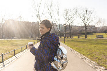 Portrait of smiling woman with backpack and coffee to go in a park, Berlin, Germany - TAMF02439