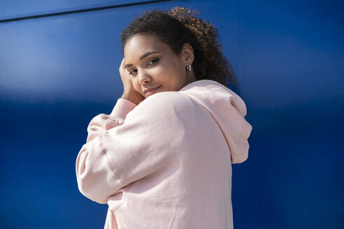 Smiling young woman wearing pink hoodie sweater in front of blue wall - SNF00420