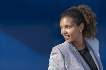 Smiling businesswoman in front of blue wall - SNF00432