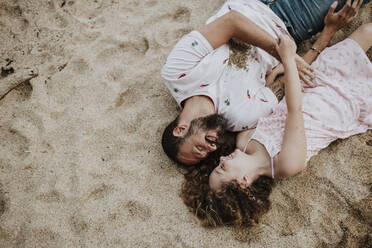Smiling father and daughter lying on beach - GMLF00331