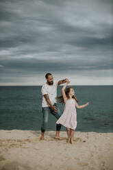 Happy father and daughter dancing on beach - GMLF00334