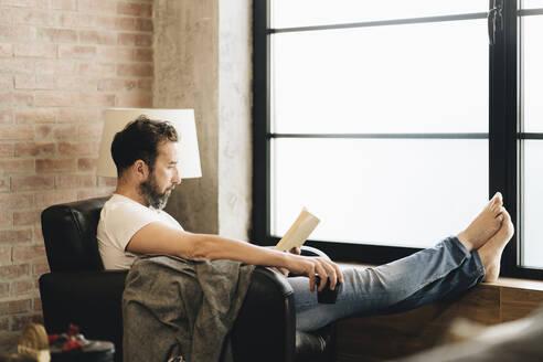 Mature man sitting barefoot in armchair, reading bok - DGOF01094