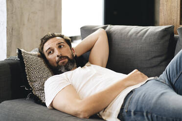Mature man lying on couch, relaxing - DGOF01097