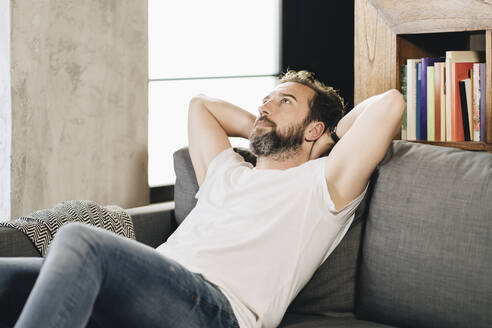 Mature man sitting on couch, contemplating - DGOF01109