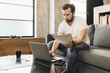 Mature man sitting on couch, using laptop, holding papers - DGOF01112