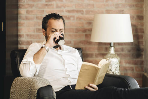 Mature man sitting in armchair, reading book, drinking coffee - DGOF01121