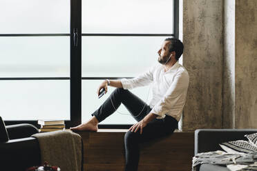 Mature man sitting barefoot on window sill, using smartphone and earphones - DGOF01127