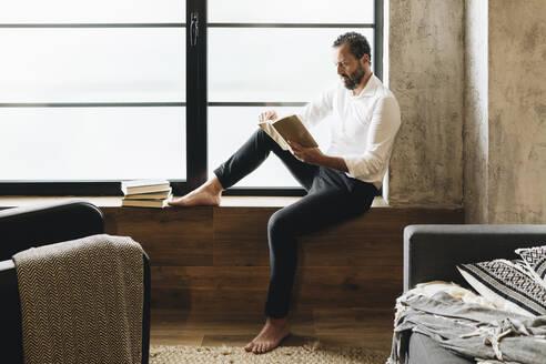 Mature man sitting barefoot on window sill, reading book - DGOF01130