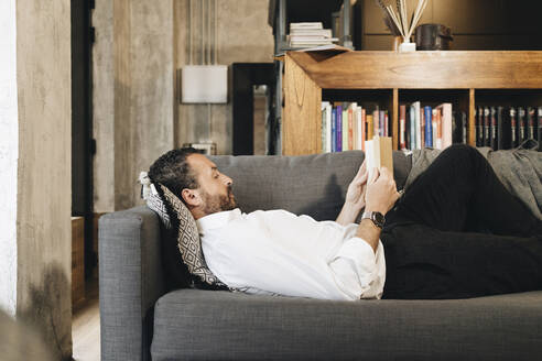 Mature man lying on couch, relaxing, reading book - DGOF01133