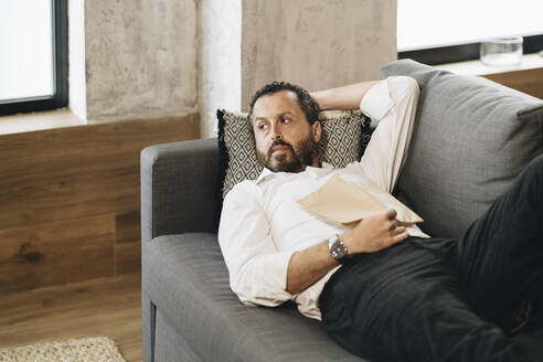 Mature man lying on couch, relaxing, reading book - DGOF01136