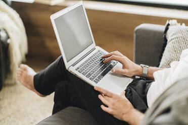 Man sitting at home, using laptop, close-up - DGOF01142