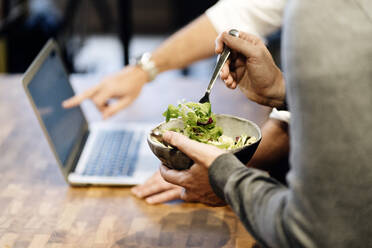Man holding bowl with salad while other one pointing at laptop - DGOF01157