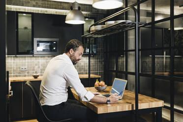 Mature businessman working in kitchen, using laptop - DGOF01166