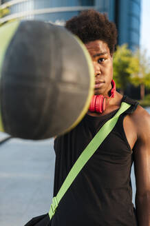 Portrait of a young man holding basketball in the city - JMPF00033