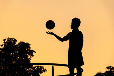 Silhouette of young man with basketball at sunset - JMPF00045