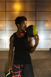 Portrait of a young man holding basketball at night with city lights - JMPF00051