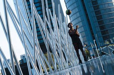 Young man playing basketball in modern city surrounding - JMPF00063
